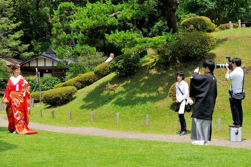 Japanese bride and groom in traditional attire taking wedding photos.  The groom is in black on the right.