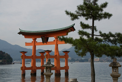 Statues and a tree near the Otorri Gate in the Itsukushima Shrine