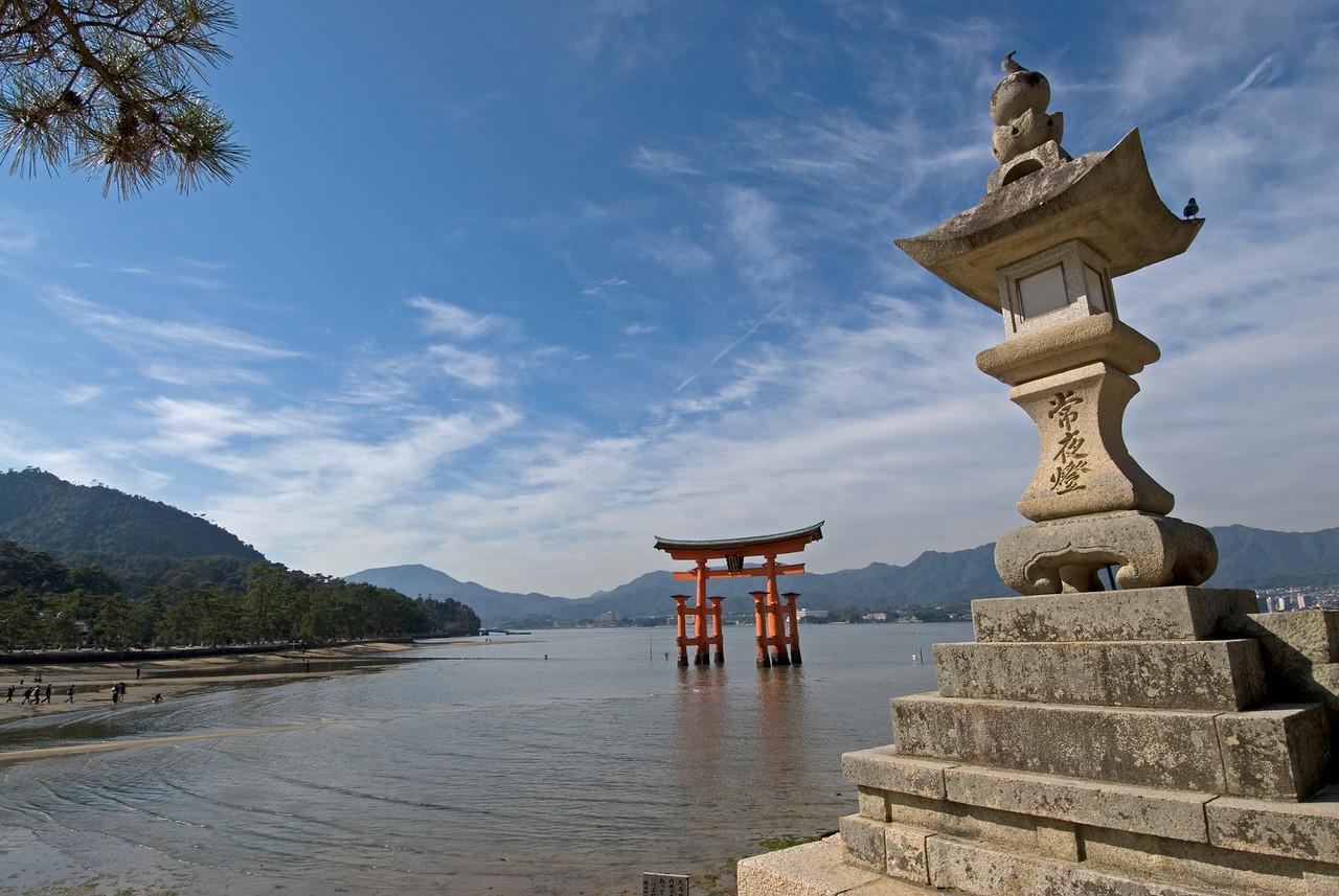 The stone lantern and Otorri Gate on a clear day in Miyajima, Japan