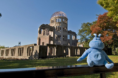 Skull posing to the camera with Atomic Bomb Dome in the background - Hiroshima, Japan