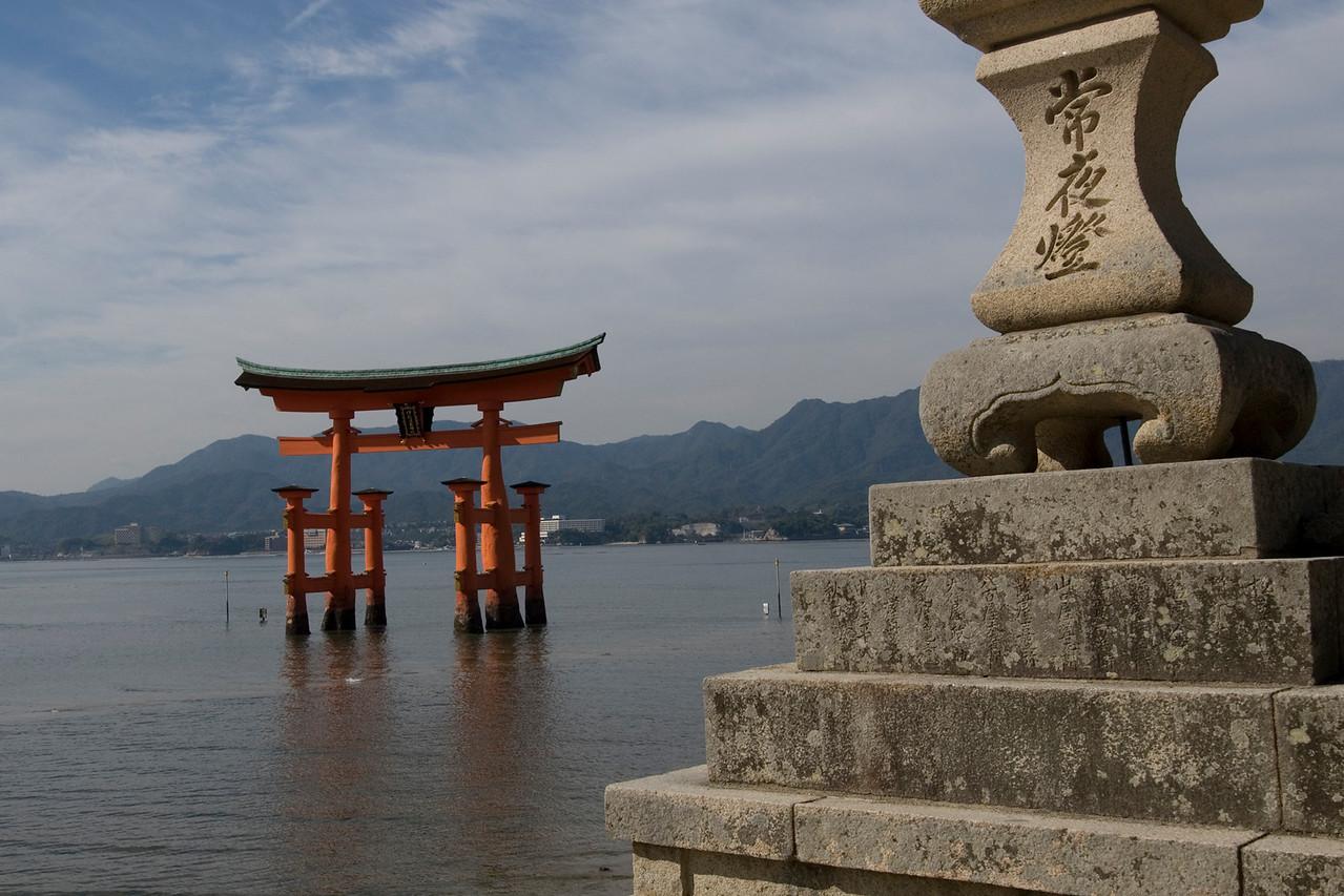 Stone lantern with Otorri Gate in the background at Itsukushima Shrine