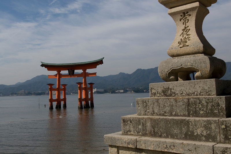 Stone lantern with Otorri Gate in the background at Itsukushima Shrine
