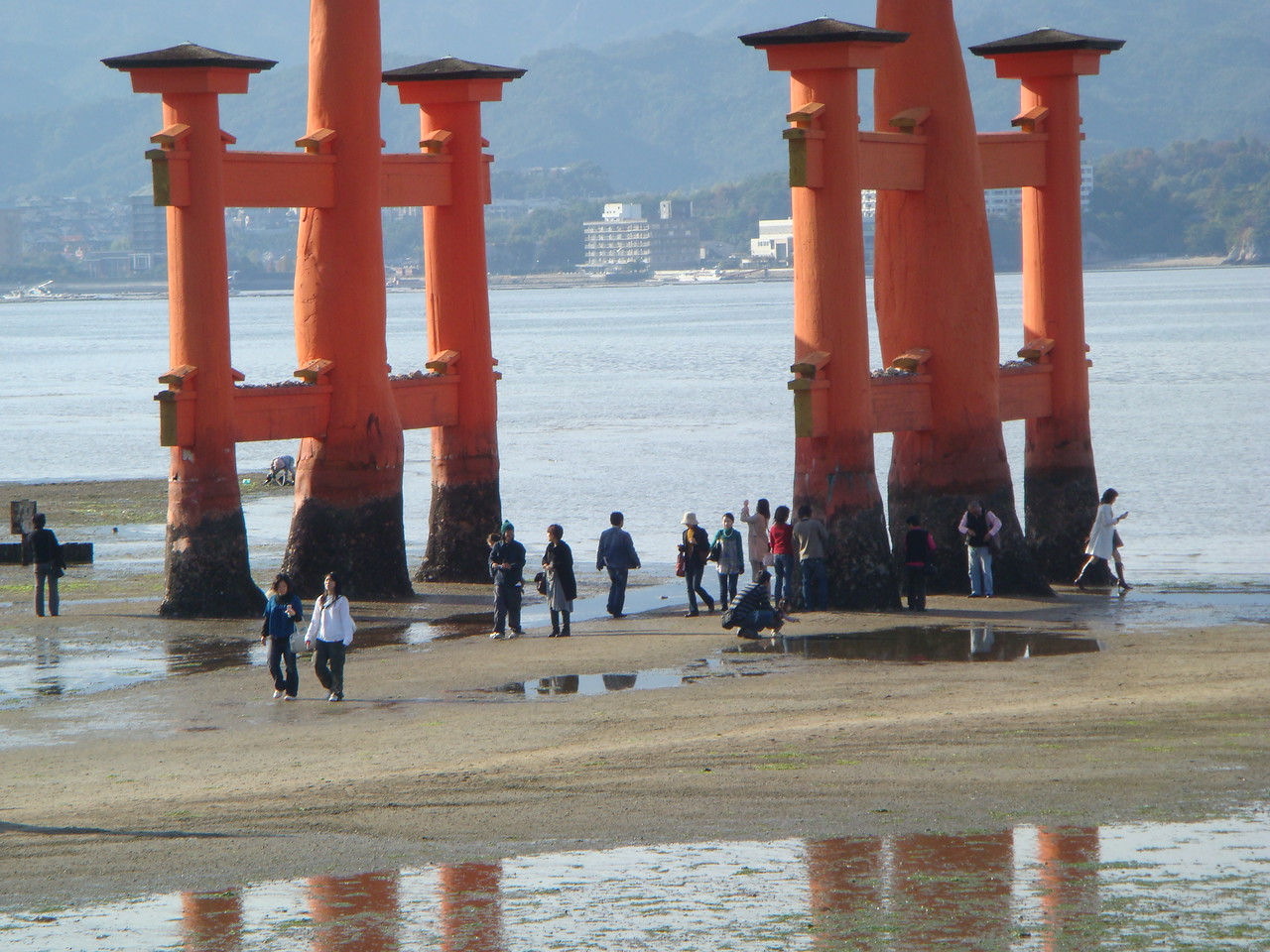 Tourists at the foot of the Otorri Gate during low tide at Itsukushima Shrine