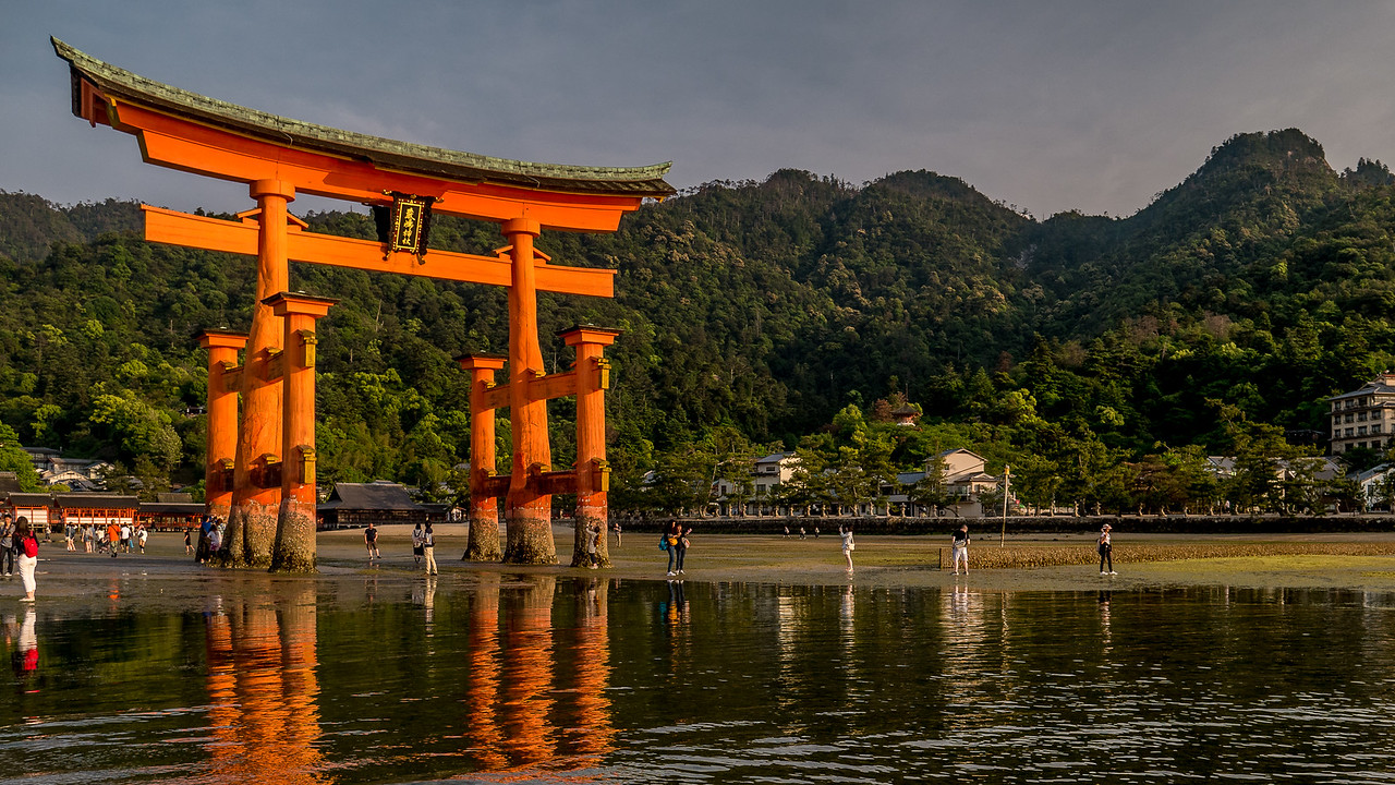 Reflections of the Itsukushima Shrine, floating torii in the water at sunset