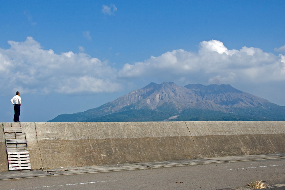 Businessman looking at Mt. Sakurajima, Kagoshima, Japan