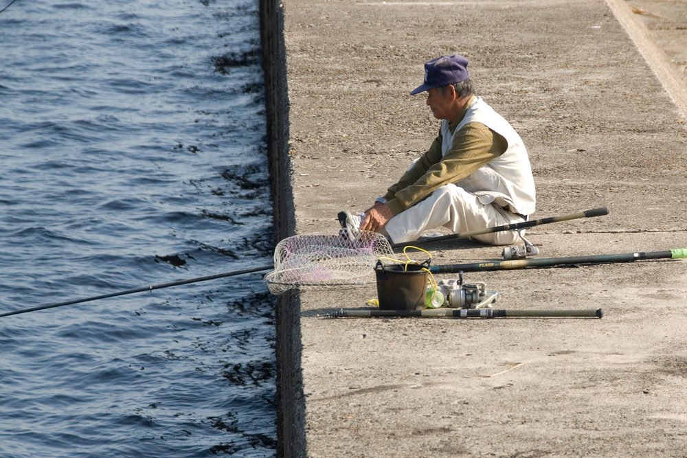 Man fishing in harbor, Kagoshima, Japan