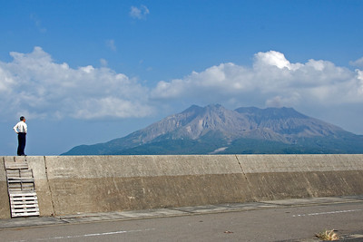 Man standing on wall with Mount Sakurajima in background