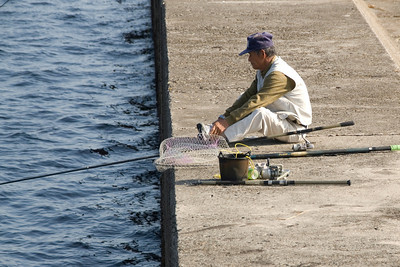 Man fishing at Harbor Wall in Kagoshima, Japan