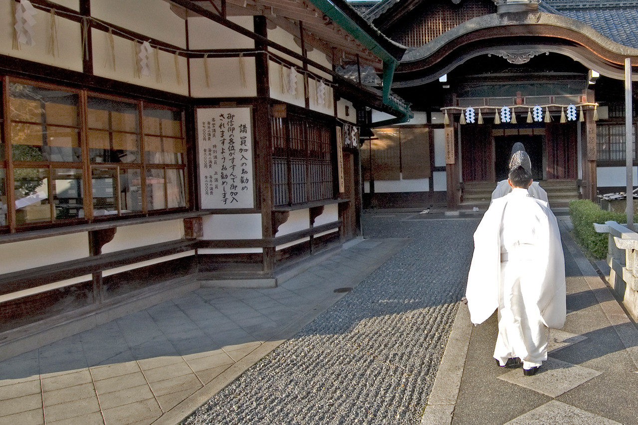 Fushimi-inari Shinto Priest walking up to the entrance in Kyoto, Japan