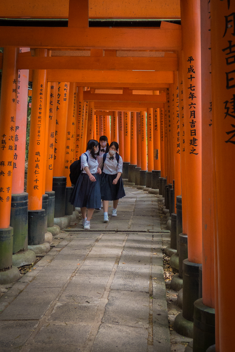 School girls walk through the iconic orange torii gates Fushimi-Inari Shrine