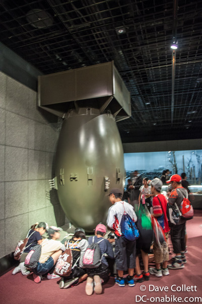 Kids writing under a replica of Fat Man, the bomb that was dropped on Nagasaki