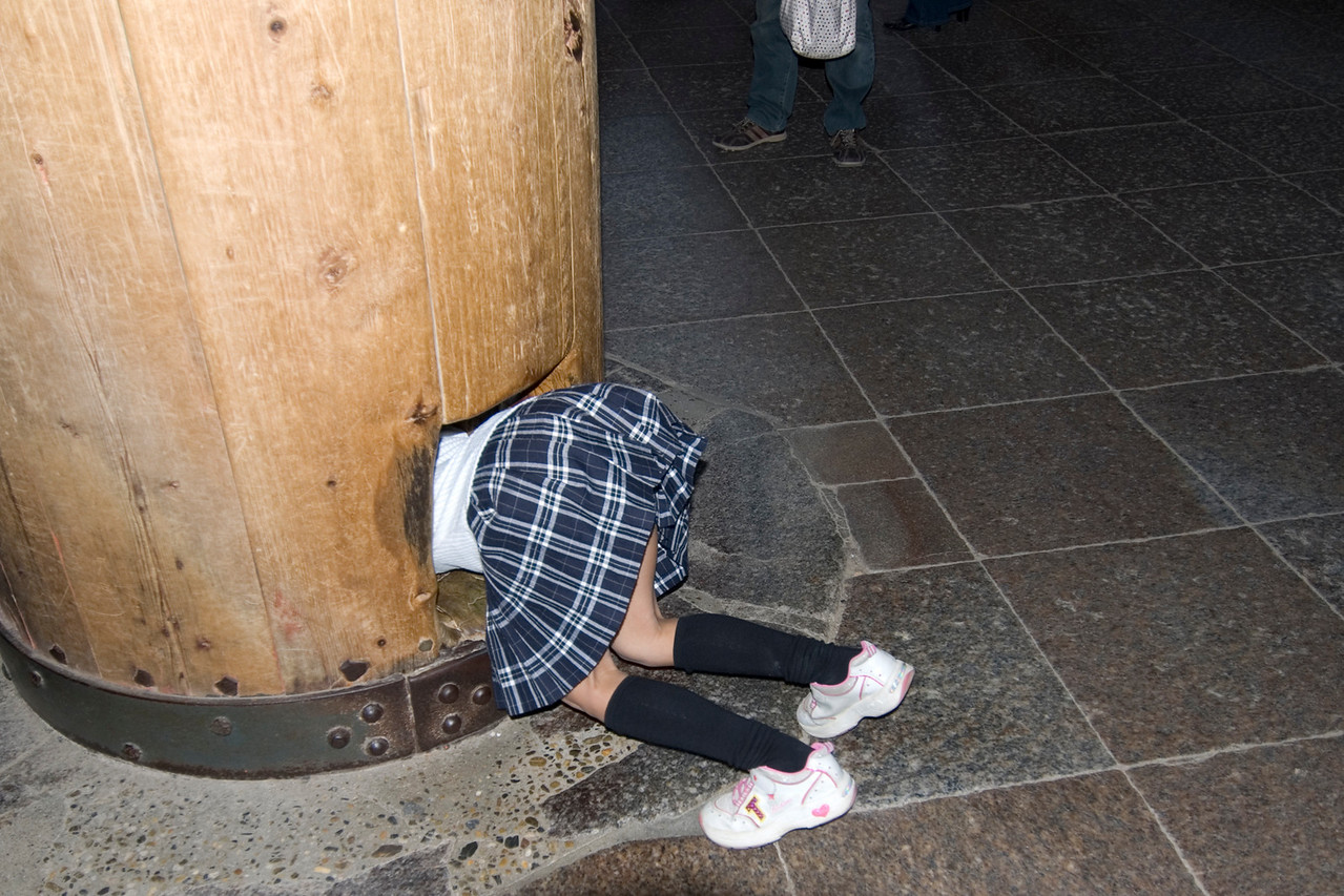 Girl crawling into a hole in Pillar, Todaiji Temple - Nara, Japan