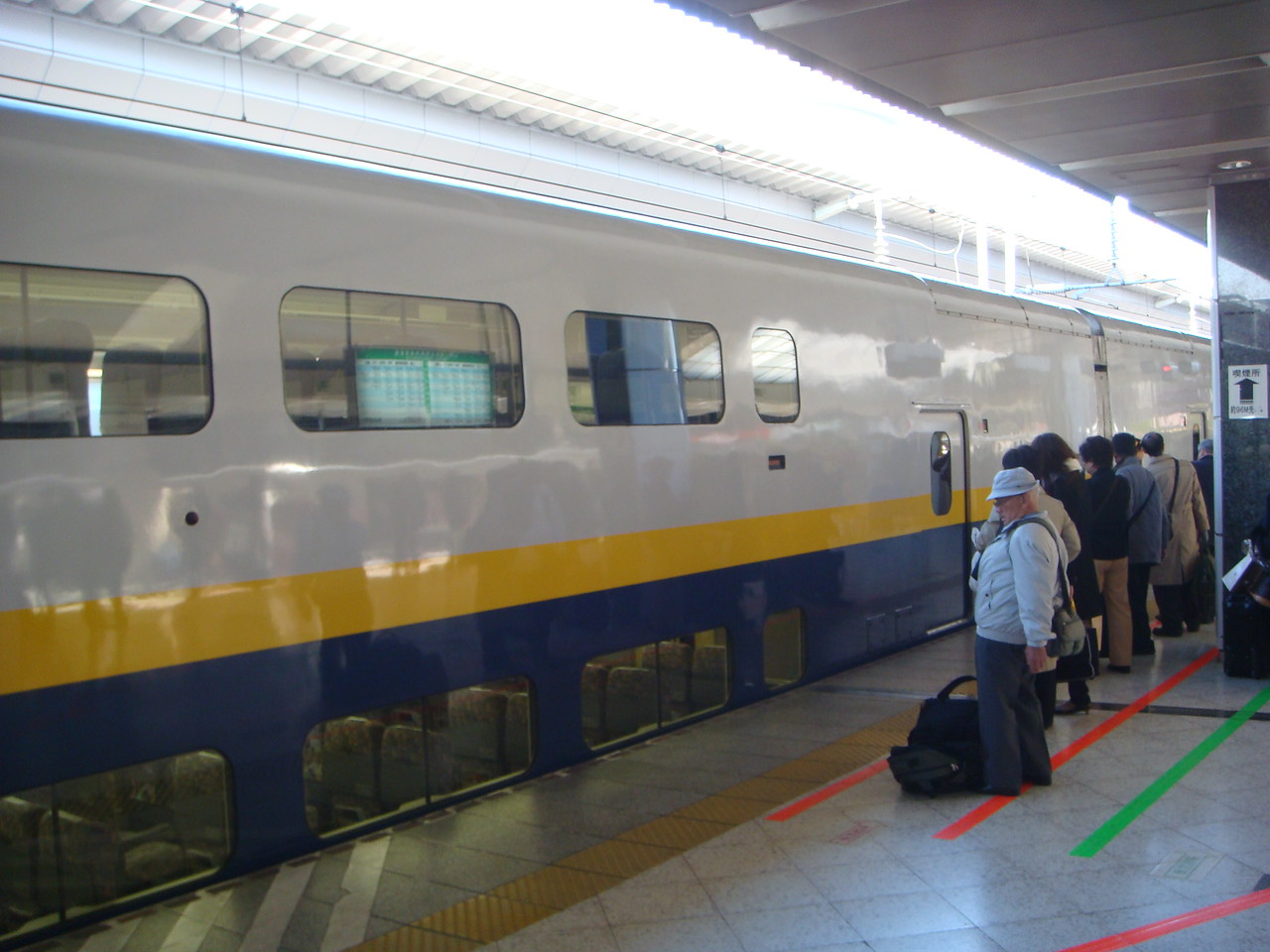 Locals and tourists waiting outside a bullet train in Tokyo, Japan