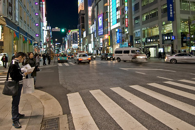 Man standing at street corner waiting to cross at Ginza, Tokyo, Japan