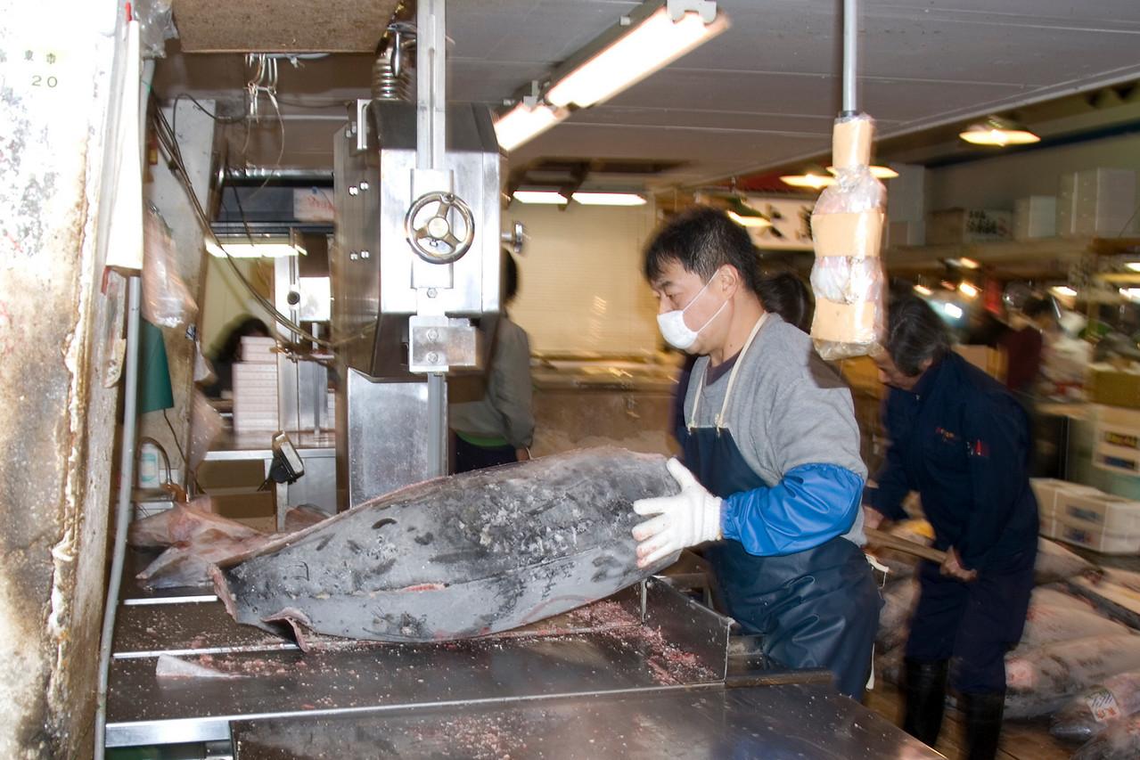 Man cutting frozen tuna with a bandsaw in Tsukiji Fish Market