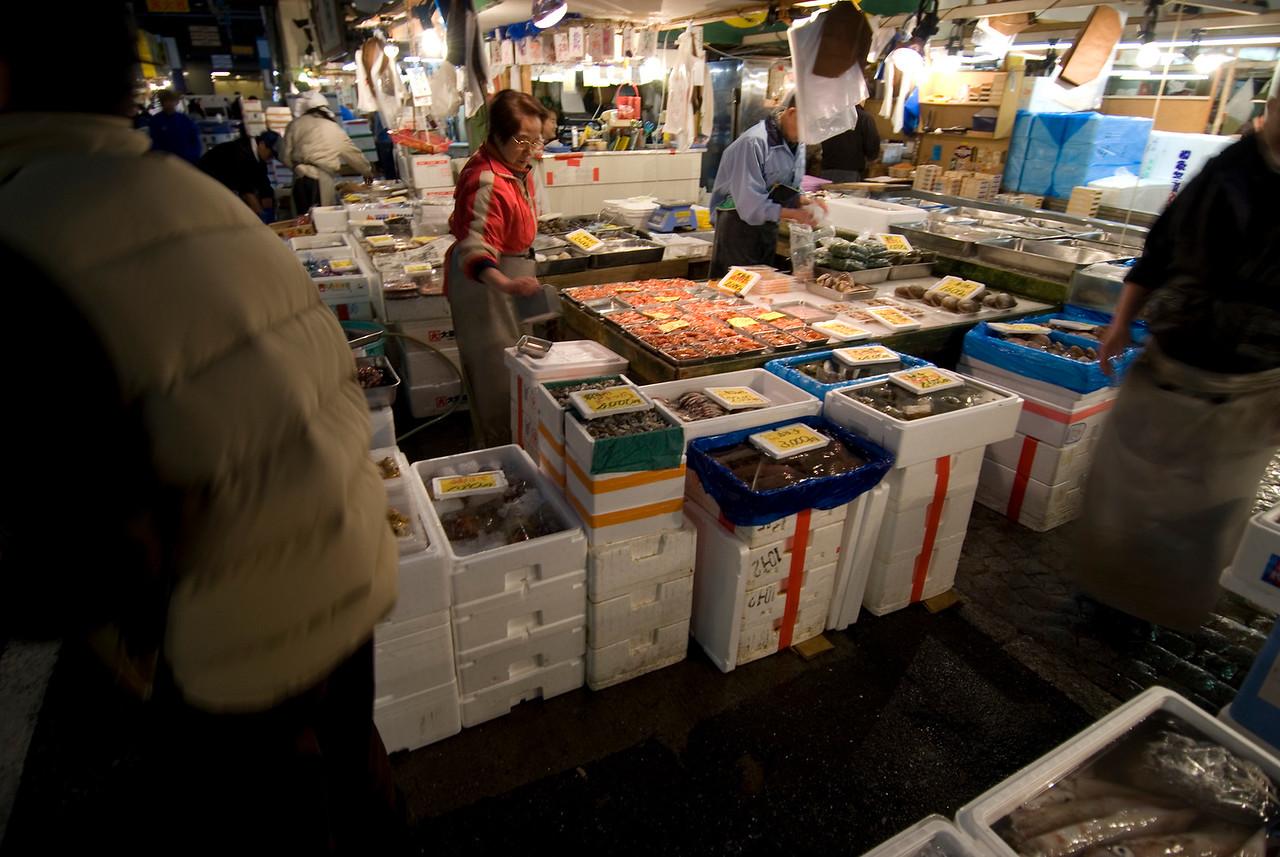 Fish Vendor checking her fish display at Tsukiji Fish Market, Tokyo, Japan