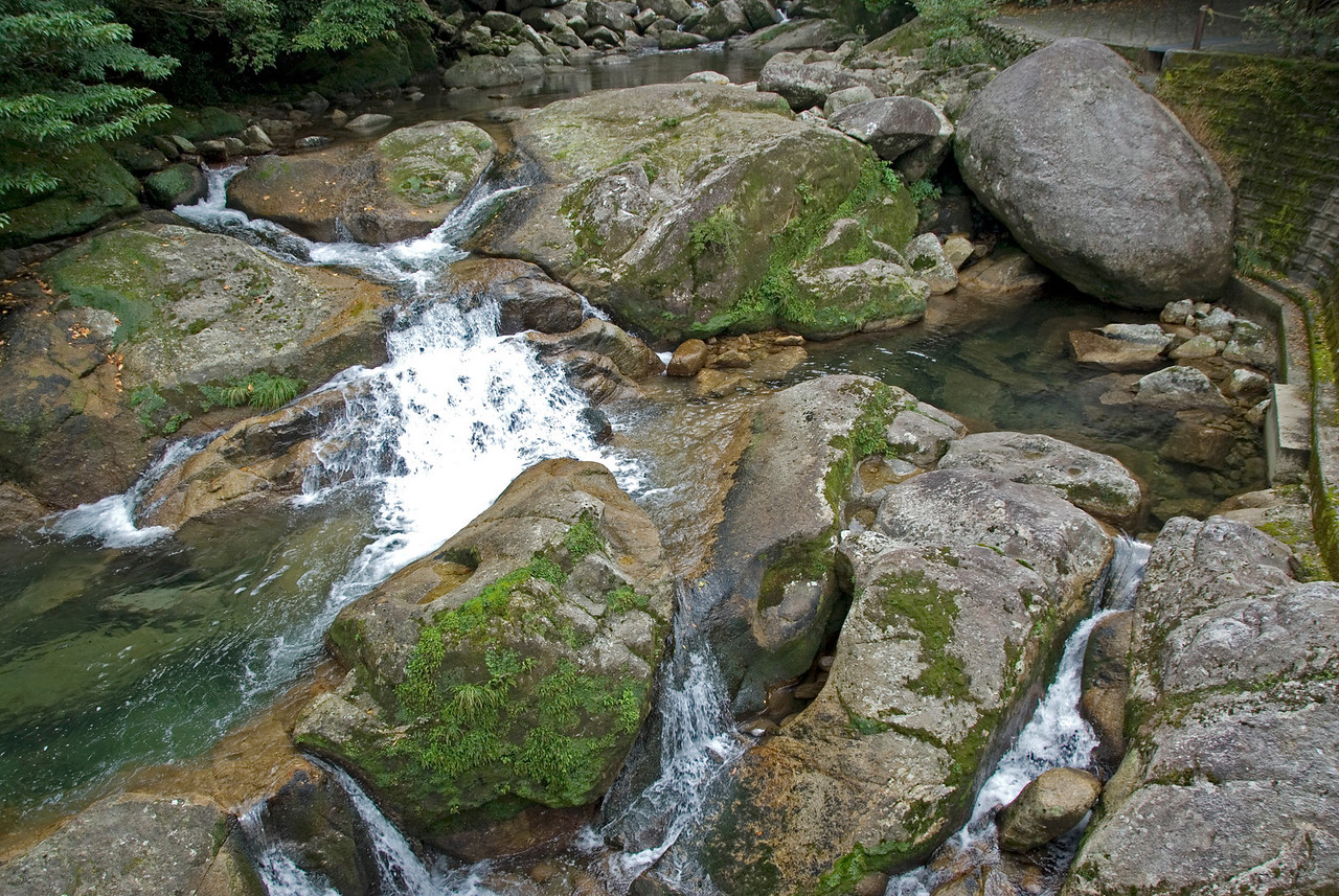 Closer look at shallow creek with moss covered rocks in Shiratani Unsuikyo in Japan