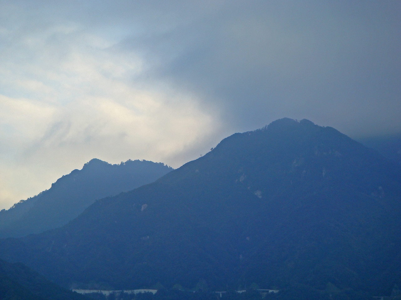 Silhouette of two mountains against foggy sky in Yakushima, Japan