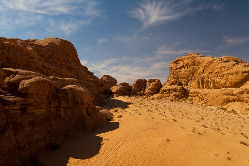 People disappear amongst the sandstone blocks of Wadi Rum, Jordan.