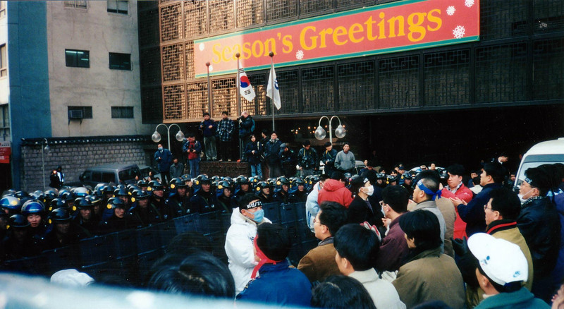 """Everyone is ready for some action, with a """"Seasons Greetings"""" sign at the Royal Hotel seemingly out of context. 1994, Seoul"""
