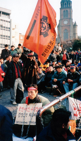 The flag says construction workers union and sign says to the former President Young-Sam Kim to resign and call him a betrayer and national disgrace. 1994, Seoul