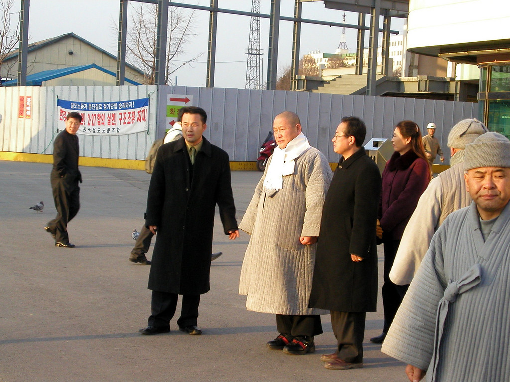 Dec 9 2002 Daejeon Train Station: The man in the long grey coat, white scarf is Gil-soo Kim. He was running for president in the 16th South Korean Presidential Election that took place on December 19, 2002. The election was won by Roh Moo-Hyun of the Millennium Democratic Party.    Gil-soo Kim only received 51,104votes, 0.2% of those who voted.  Given the few people who were there to listen too him on that day in front of the train station, the results do not seem surprising.<br /> <br /> The election was won by Roh Moo-Hyun of the Millennium Democratic Party.