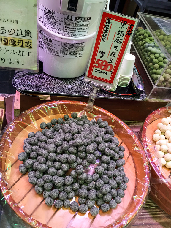 Black sesame covered peanuts at a food market in Kyoto Japan