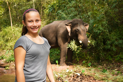 Ana is psyched to watch the elephant relax and eat near the river.