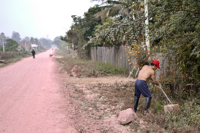 A worker digs on the roadside in rural Laos.