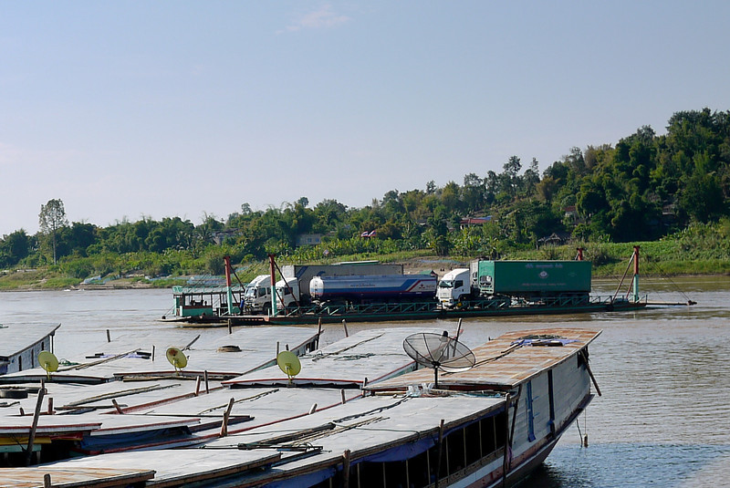 Several huge semi truks wait to cross over the Mekong River from Thailand into Laos at the border crossing between Chiang Khong and Houay Xai.