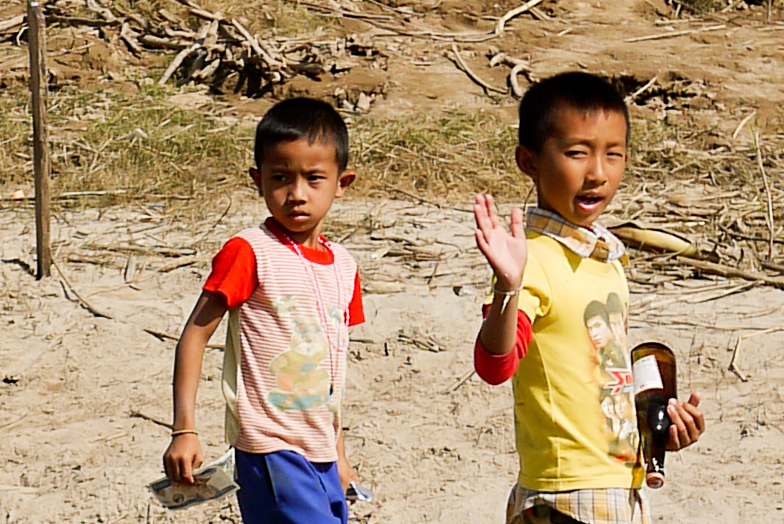 Young boys board the slow boat to sell snacks on the way to Luang Prabang, Laos.