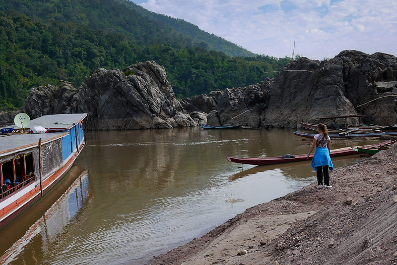 Ana takes some time to skip rocks on the banks of the Mekong River as we travel down to Luang Prabang.