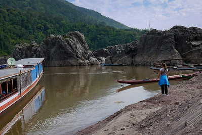 Ana takes some time to skip rocks on the banks of the Mekong River as we travel down to Luang Prabang.