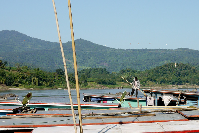 Satellite dishes adorn some of the slow boats in an odd display of modernity as a man extracts his own boat from the tangle of docked slow boats.