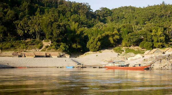 The orange-tinted banks of late afternoon on the Mekong River in Laos.