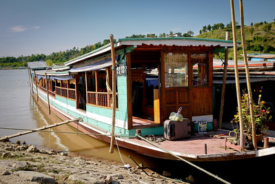 A long wooden slow boat, filled with old bus seats for the long trip down the Mekong River in Laos.