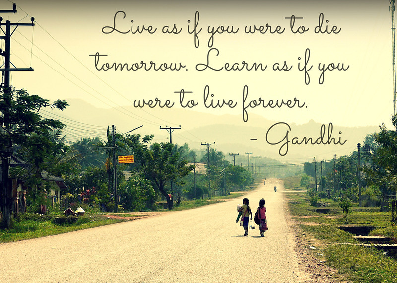 A quote by Mahatma Gandhi about learning on an image of two young school girls in rural Laos.