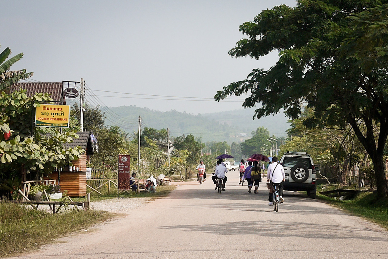 A large group of children with umbrellas and bikes head home from school in the late afternoon in Laos.