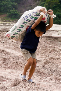 A young boy hauls some heavy goods to the shoreline to the waiting slow boat.