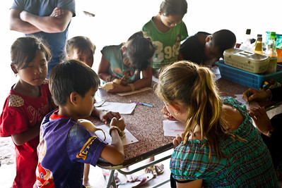 Ana and the children in Tha Suang bond over a box of colored pencils and some paper, Laos.