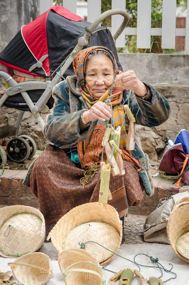 Old woman selling trinkets made of bamboo.