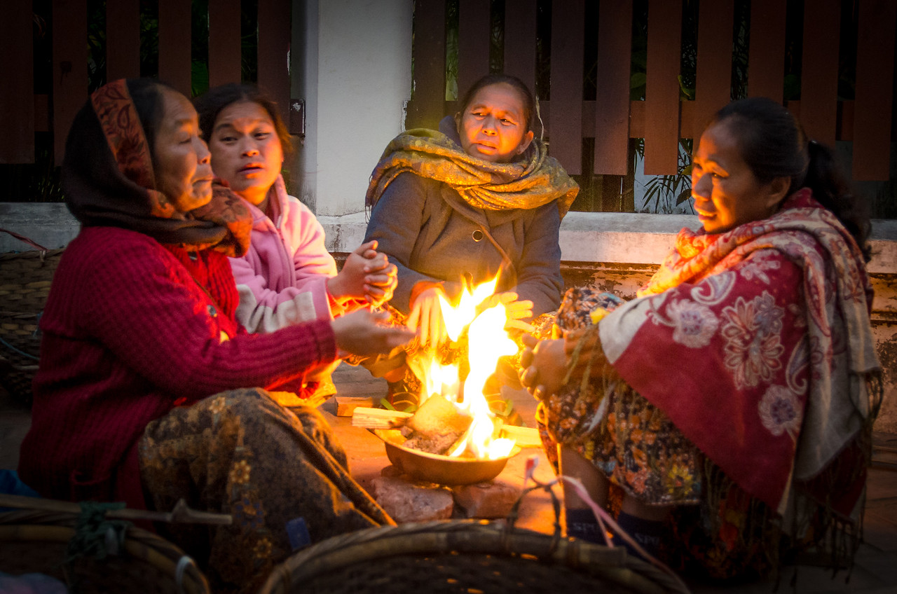 A group of women chat and keep warm by the fire before the market gets busy.