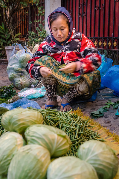 Woman selling cabbage and green beans.