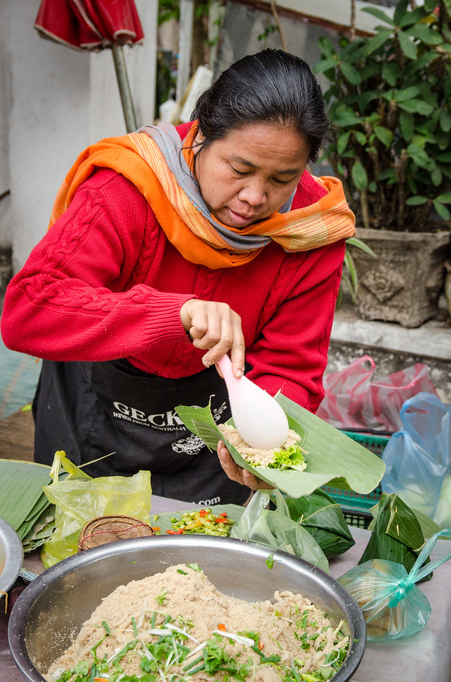 This woman is preparing snacks in banana leaves, traditional Lao style.