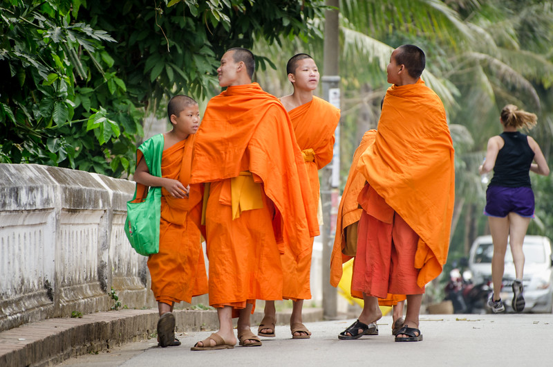 Young monks on the street as a western girl jogs by.