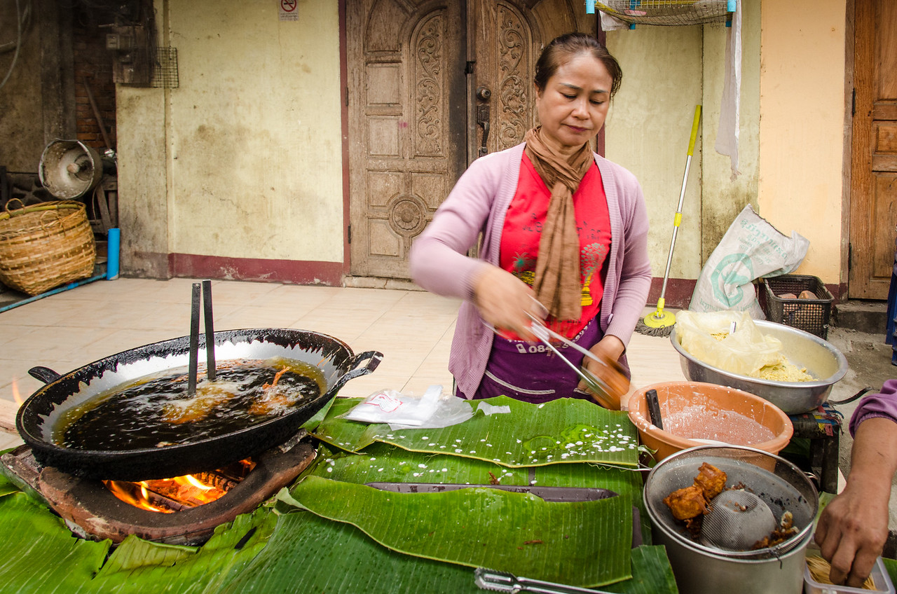 A woman making fried snacks. Note the banana leaf counter top.