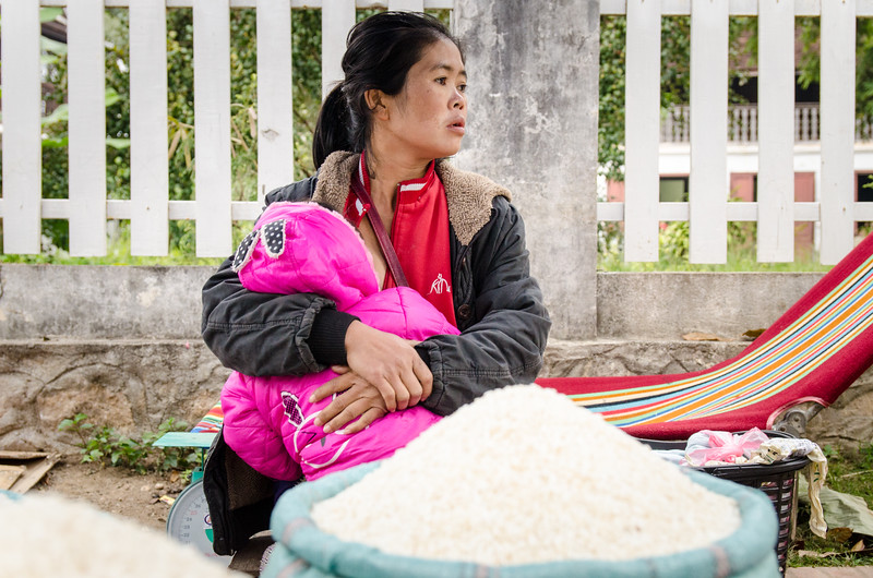 Woman sellig rice with her baby.