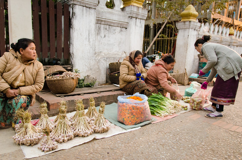 Women selling garlic, spring onions and merigolds.