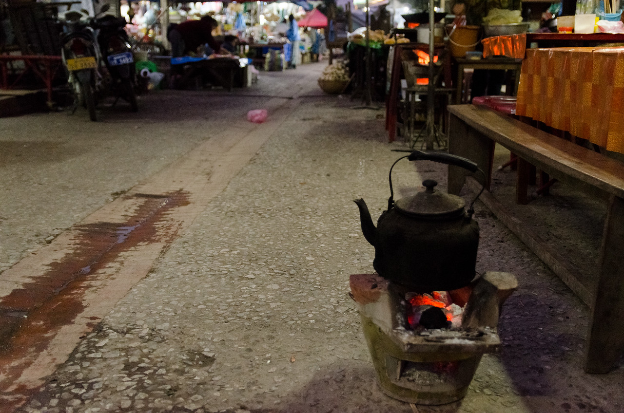A kettle warms over a fire on a street in the market before dawn.