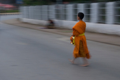 Young monk walking barefoot on the street of Luang Prabang, Laos